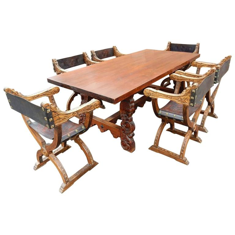 Spanish Colonial Dining Table With Six Elaborate Carved Wood And Leather Chairs For Sale