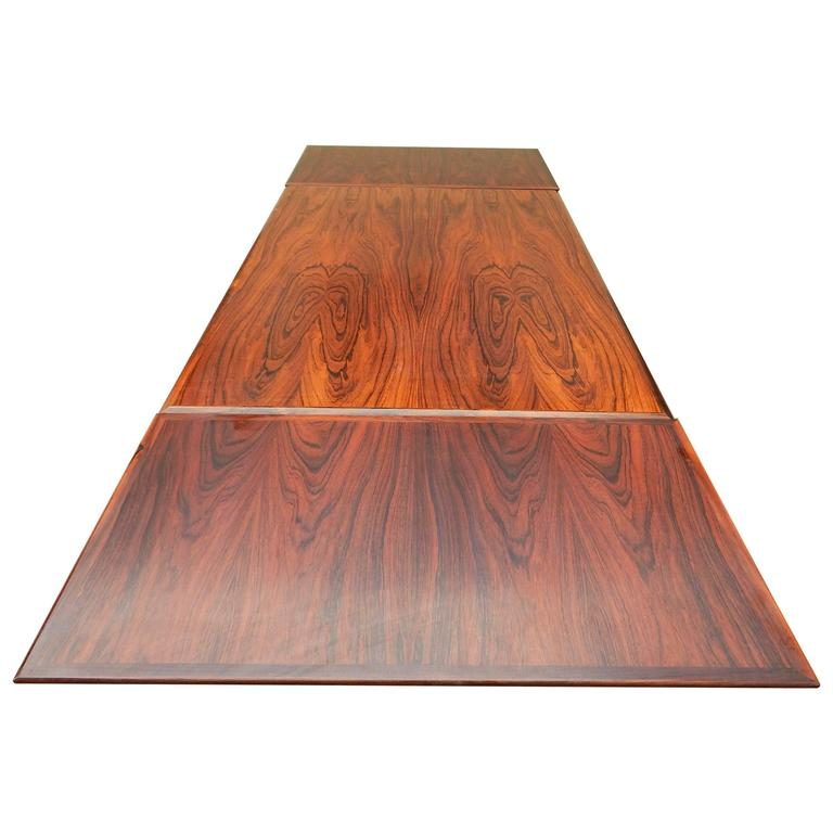 """Danish Mid-Century Modern extendable dining table rendered in highly figured rosewood. Two leaves are stored within the top of the table and pull-out with ease. Each leaf is 22"""" wide. Unextended the table length is 55"""". With leaves pulled"""