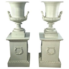 Pair of 19th Century French Cast Iron Masked Urns on Tall Plinths