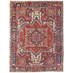 Antique Persian Heriz Carpet with Stylized Central Medallion in Warm Hues of Red