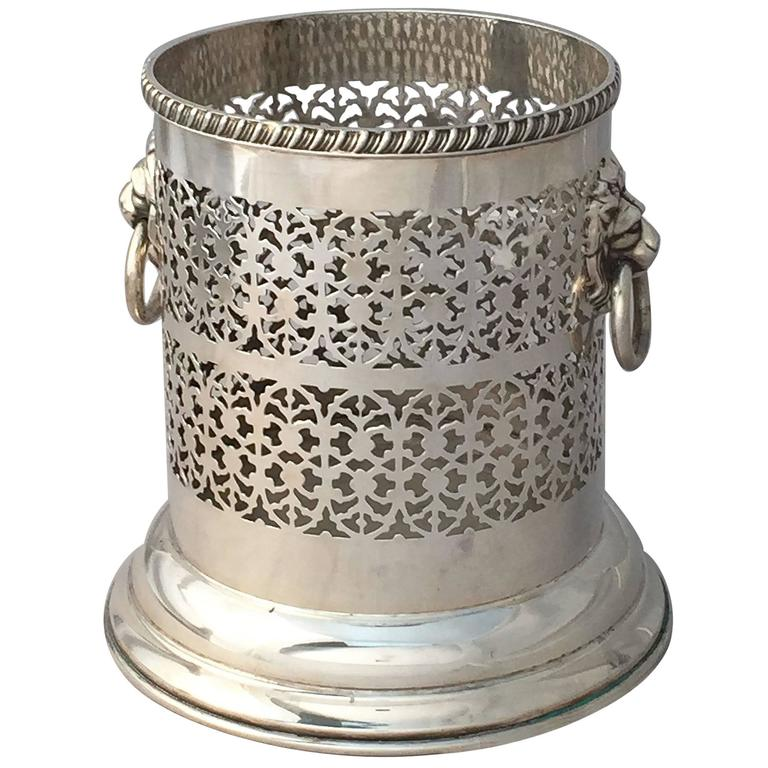 A fine English wine bottle display holder or coaster of plate silver, featuring a pierced design around the circumference and opposing Regency lion ring pull handles, with rolled edge around the top.
