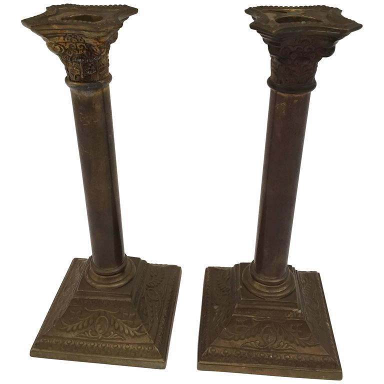 A very nice pair of George III neoclassical style brass candlesticks with square bases and columnar shafts supporting urn form candle cups. The candlestick are in form of columns, the bases and top are square with neoclassical ornate designs. Nice