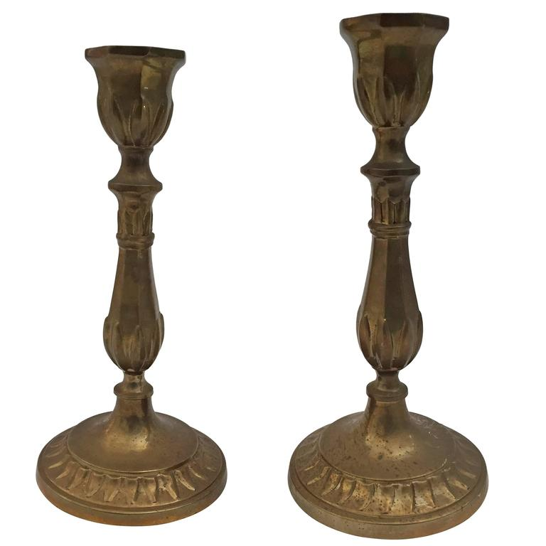 A pair of French polished candlesticks in great patinated brass. Engraved brass with round base. Great brass decorative art objects.