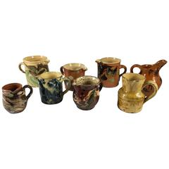 Collection of Eight Small French Provincial Jaspe Cream Pitchers, 19th Century