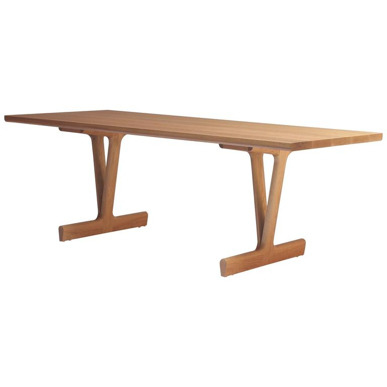 The IV Dining Table was designed by Justin Godar in 2017. The unique leg design provides sturdy support while offering a wide range of seating options. Made in San Francisco from solid white oak and finished in a hardwax oil.   Also shown in walnut