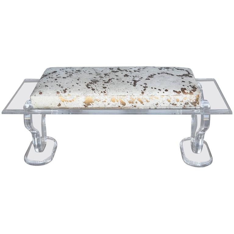 lucite bench with gold splatter cowhide upholstery for