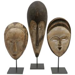 Set of Three African Hand-Carved and Painted Wood Masks on Metal Stands