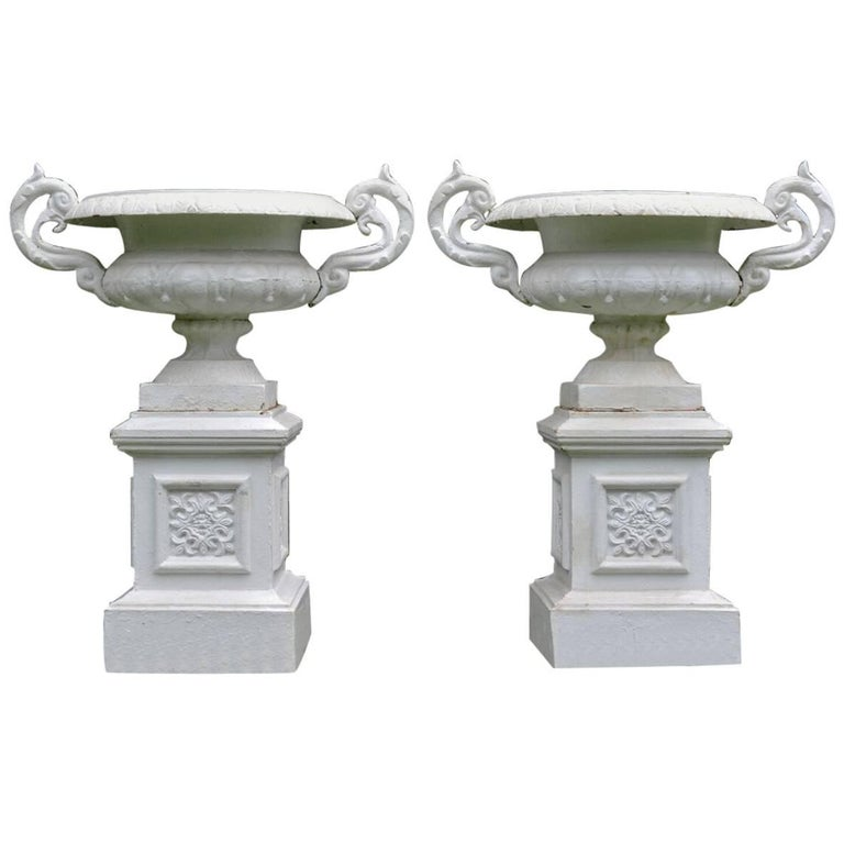 A Pair of White Painted Cast-Iron Urns on Pedestals