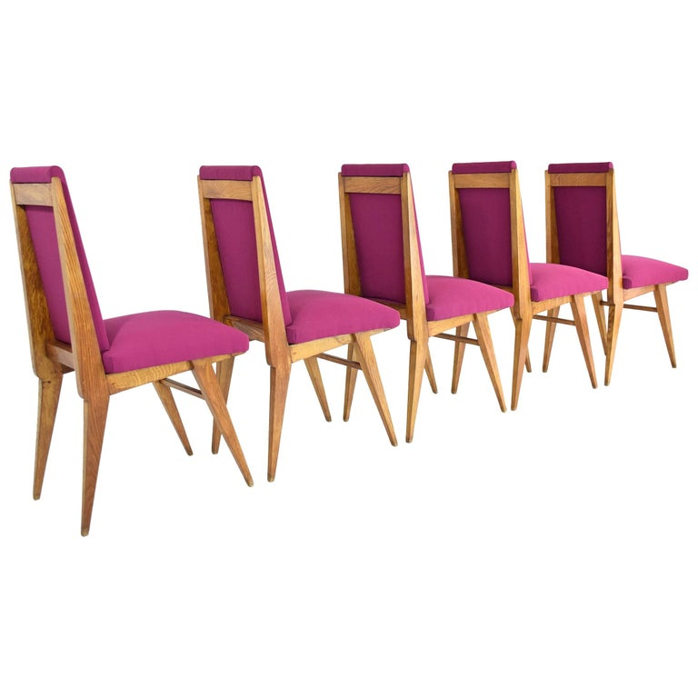 French 20th century vintage high back art deco dining chairs composed of solid oak and splayed -  tapered legs in the style of Charles Dudouyt.   Entirely restored with a high quality pink Lelievre Paris fabric and meticulous re-finishing.  France.