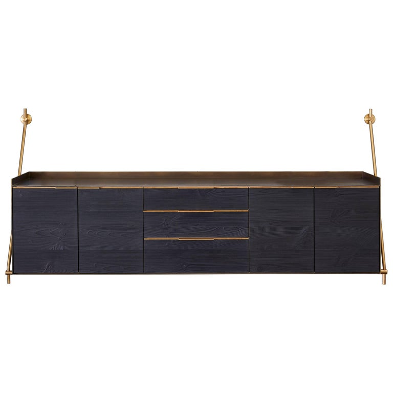 Amuneal's wall hanging credenza is supported by our traditional collector's shelving hardware in a warm brass finish. The credenza itself is clad in solid bronze with a deep, mottled, patinated finish with golden highlighted edges. The structure of