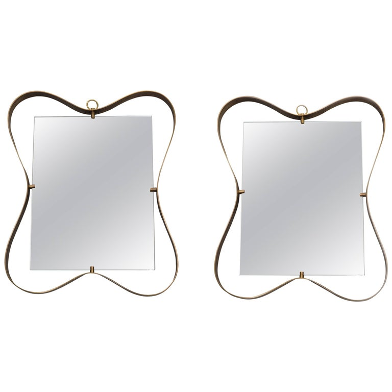 Fontana Arte pair of whimsical and elegant mirrors with curved patinated brass frame holding beveled mirrored glass, Italy, circa 1950.  Priced at $6,500 for each mirror.  Literature Lastre di Vetro e Cristallo, No. 10, August 1950