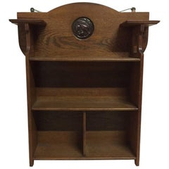 Shapland and Petter, an Arts & Crafts Hanging Oak Bookcase with Copper Plaque