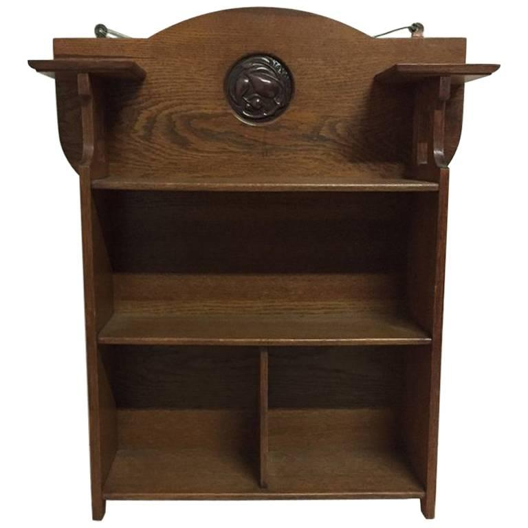 Shapland and Petter, an Arts & Crafts Hanging Oak Bookcase with Copper Plaque For Sale