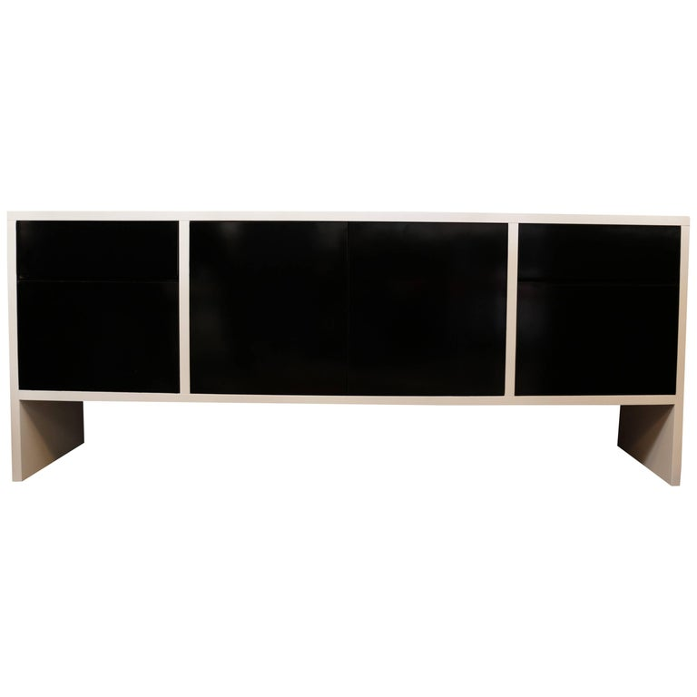 Newly refinished white lacquered credenza has contrasting black doors. The doors conceal two shelves in the middle and there are four drawers, one larger and one smaller on either side.