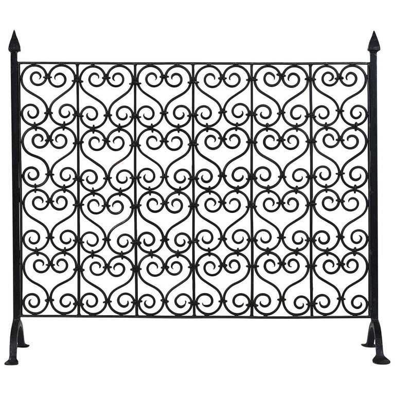 For Sale on 1stdibs - This 1900s French Baroque-style fireplace screen is made of wrought iron with a dark finish. The screen features a repetitive S-shaped scroll pattern.