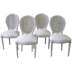 Set of Four Louis XVI Carved and Painted French Cane Back Dining Chairs