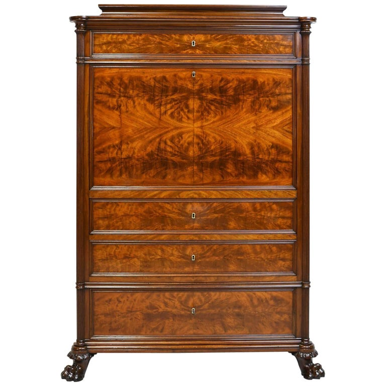 An extremely handsome secretary in fine West Indies mahogany with pedestal top above top drawer, and a birch inlaid drop-front opening to a desk with a long open storage area for papers below a series of fitted drawers that are in mahogany banded in