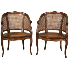 Pair of Caned Walnut Stained Bergeres