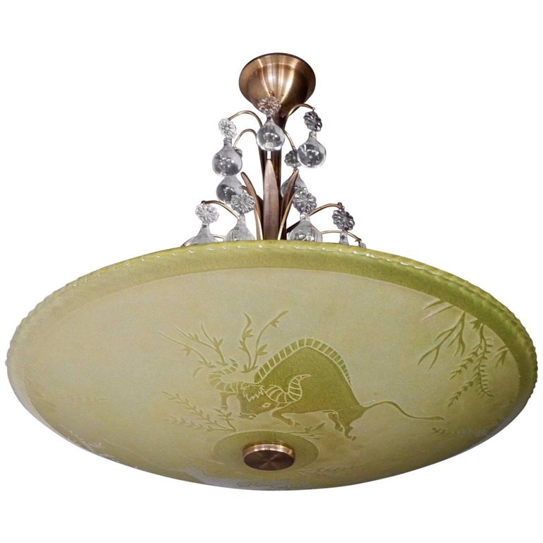 Swedish Art Deco era hanging bowl etched glass hanging fixture. The glass glows a beautiful yellow and has etched bull motifs. With hanging pear drop crystals over the glass bowl. With three standard base sockets. Price includes complete rewiring.