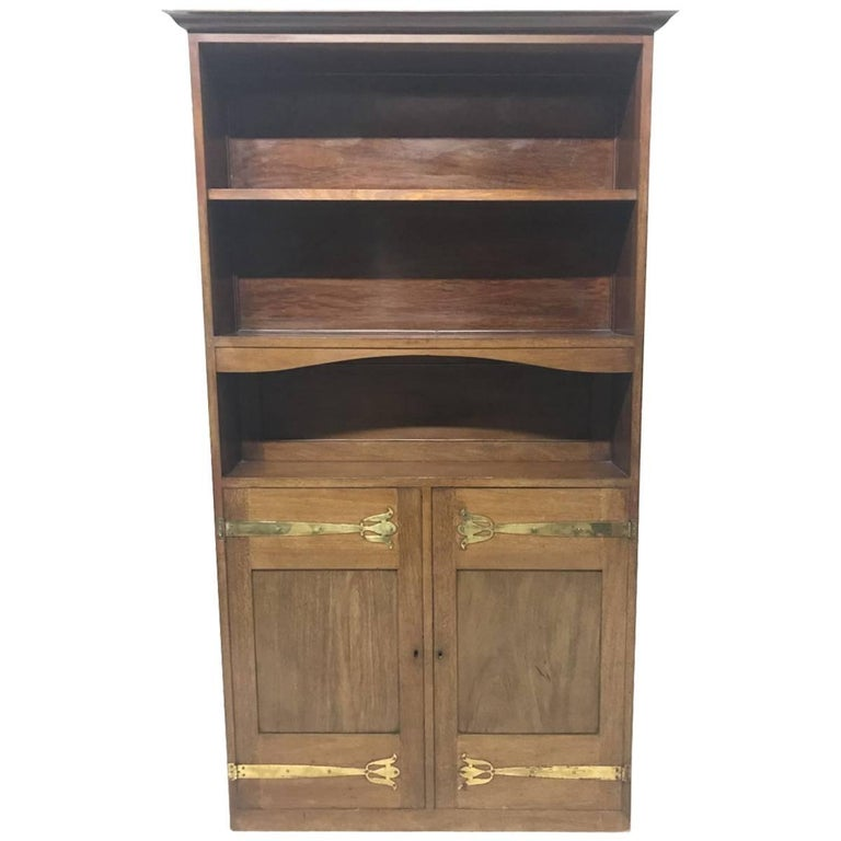 Liberty & Co. A Slim Arts & Crafts Walnut Bookcase with Stylised Copper Hinges For Sale