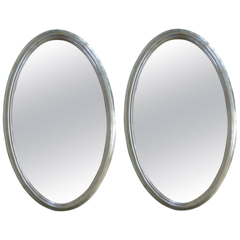 Pair of Large Oval Silver Giltwood Mirrors