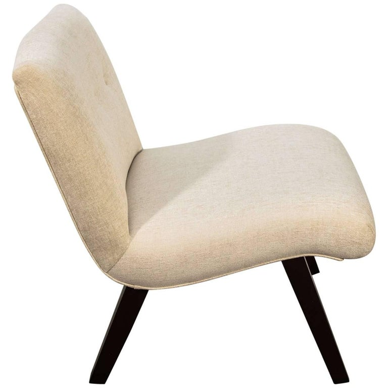 Mid-Century Modern lounge chair with scoop design. Chair has dark walnut wood legs with splayed design. Upholstered in woven crème colored chenille. Features button accents and self-welt details.