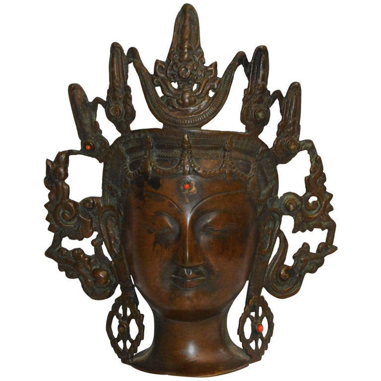 This is a Thai bronze head figurine with an ornate open work headdress. She has elongated ears with decorative earrings and a scallop border around her face. Red beads decorate her forehead and her left earring. It is marked India on the back.