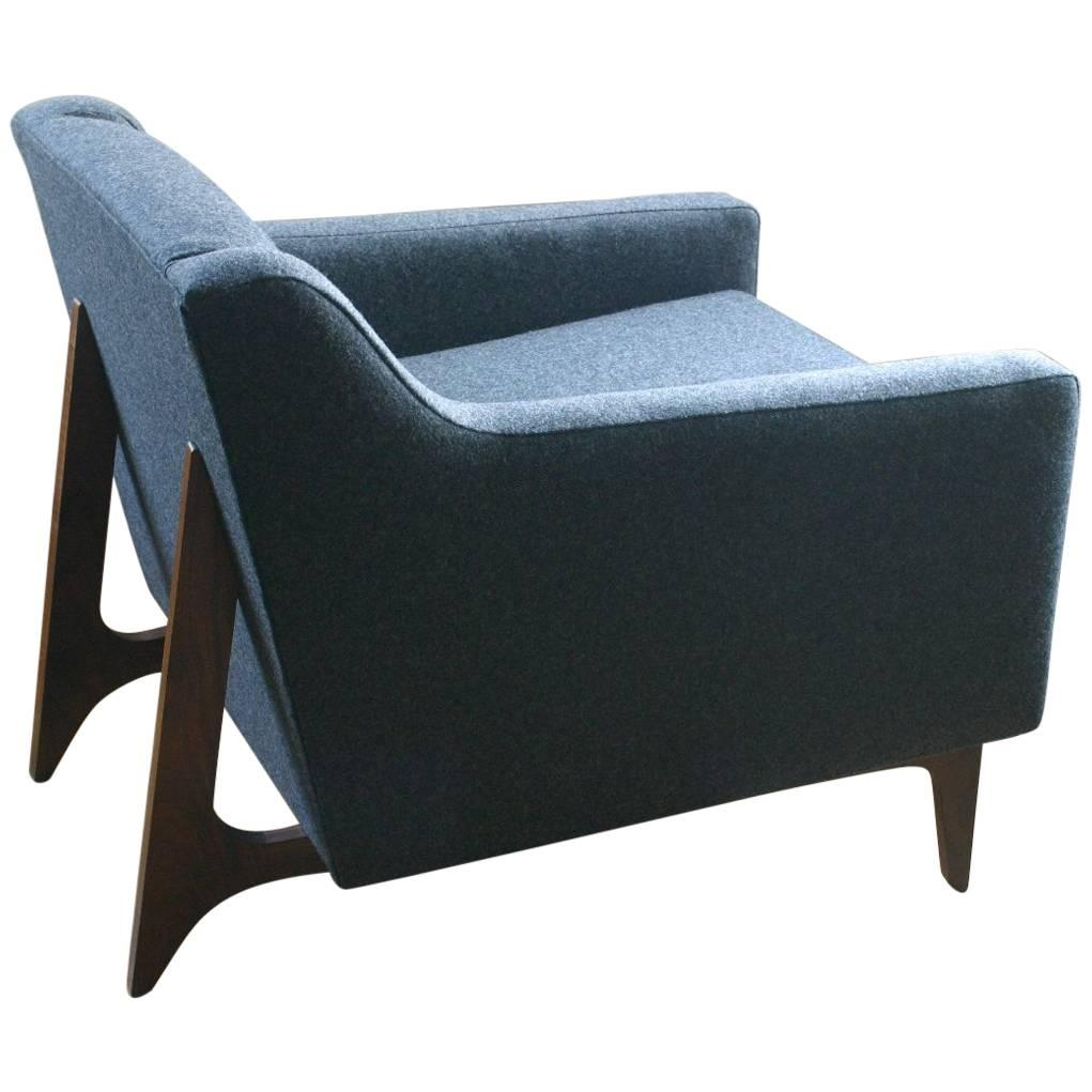 modern upholstered lounge chair with walnut base and tufted seat back