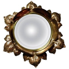 An Arts & Crafts Circular Copper Bevelled Mirror in the Form of a Flower Bud