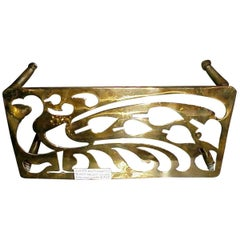 An Aesthetic Movement Brass Trivet with Peacock Fret Work, on Turned Legs