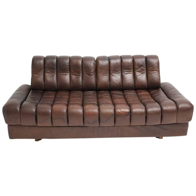 This vintage leather love seat has a special feature - to unfold by one hand into a daybed for two persons.