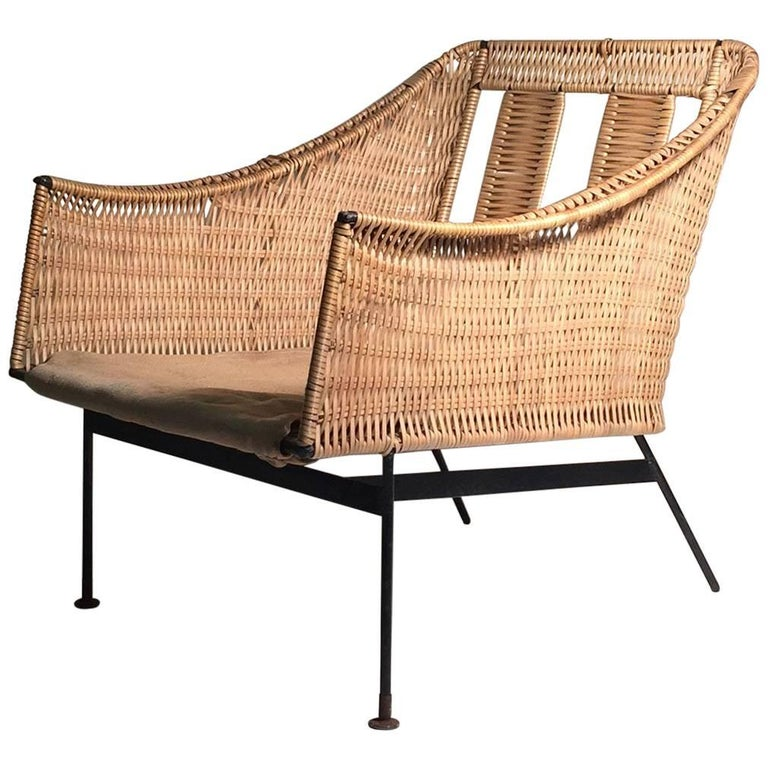Uncommon early form by Tempestini for Salterini. Wrought iron with a faux wicker or rattan in a plastic of sort. A nice example of Tempestini's period design. Just needs cushions. Some mild wear to frame. A couple areas on the plastic wrap that