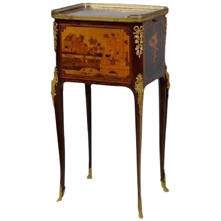 This exquisite marquetry occasional table was crafted in France in the 19th Century, and fashioned in the Transitional style, incorporating both Neoclassical and Rococo elements. The table is set on four gilt bronze hoof feet, which extend upward to