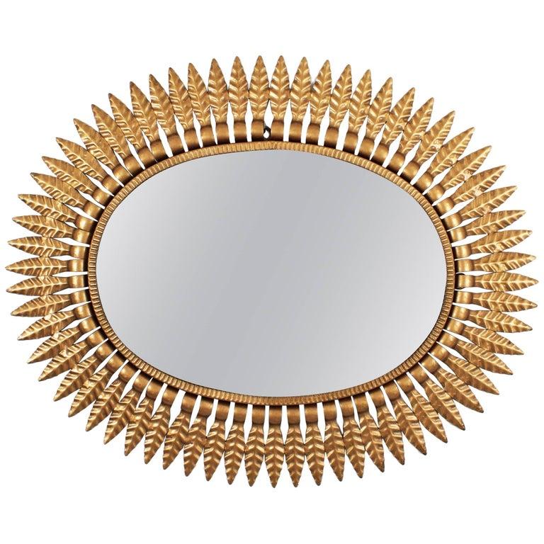 Spanish Mid-Century Modern Gilded Metal Oval Sunburst Mirror For Sale