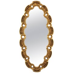 Large Francisco Hurtado Scalloped Giltwood Oval Mirror with Carved Scroll-Work