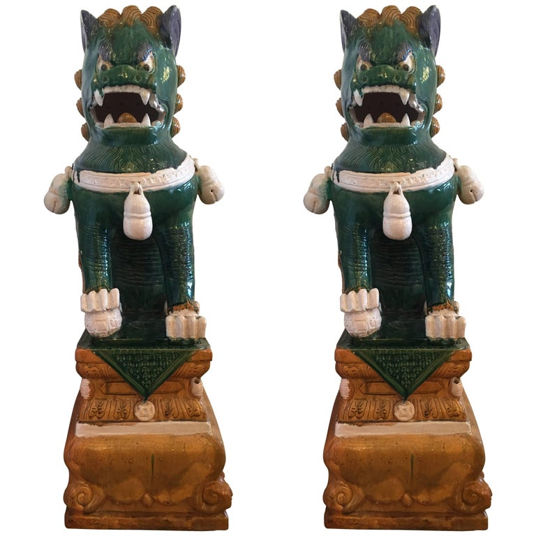 Gargantuan dramatic pair of green and ochre Chinese foo dogs, having a luscious glaze over clay.