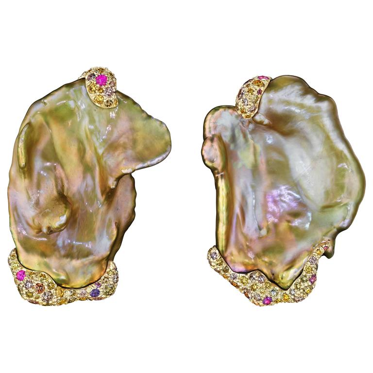 These eye-catching earrings feature a pair of Chinese freshwater pearls accentuated by multicolored diamonds and sapphires set in 18K yellow gold.  Internationally award winning designer Naomi Sarna creates gem carvings and jewels of unusual beauty.