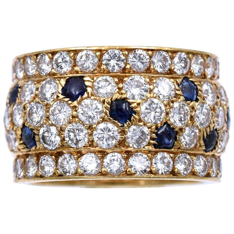 Diamond and sapphire 'Panther' ring, Cartier, France. The band ring set with round diamonds weighing approximately 5.60 carats, with buff-top sapphire accents,  Ring size is 6.1/4 Signed Cartier, and # 609476, with French assay and maker's marks.