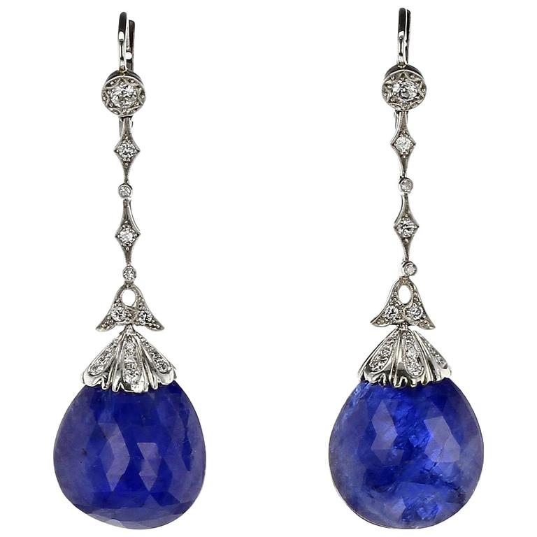 A stunning and bold pair of natural, no-heat sapphire briolette-cut drops suspended from a diamond-studded cap and mounting with alternating star shape and round bezel-set diamonds, with milgrain work. The two sapphires weigh an approximately