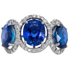 1970s Burma Sapphire Three-Stone Platinum Ring with Diamond Halo