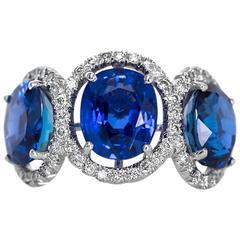 1970s Burma Sapphire 3-Stone Platinum Ring with Diamond Halo
