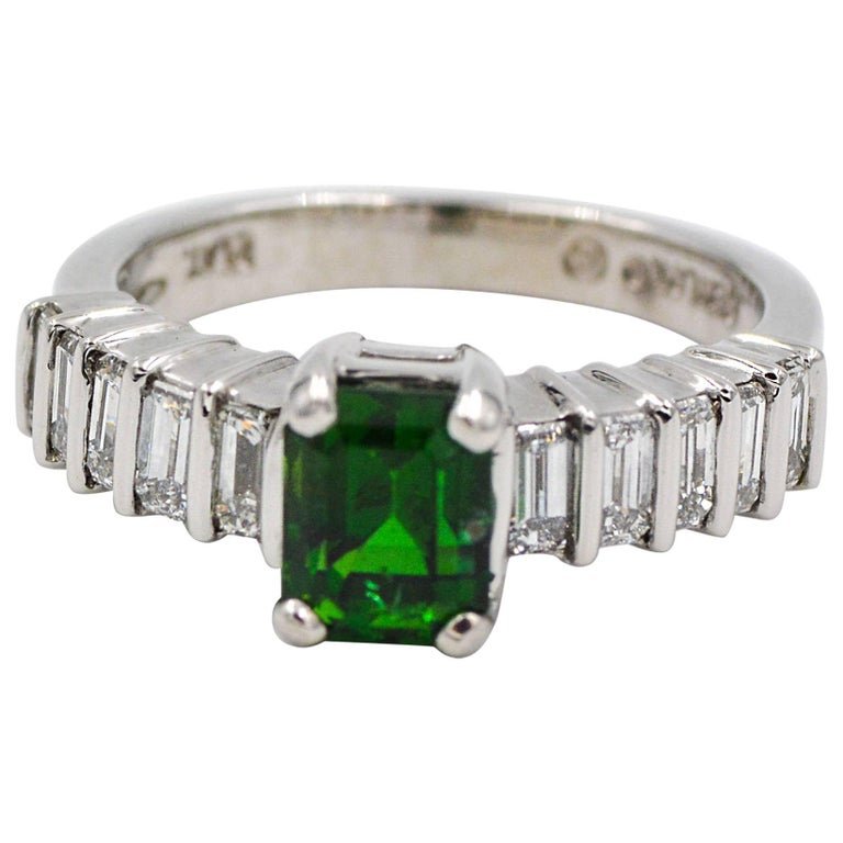 This beautiful platinum ring is centered by a vivid green emerald cut tourmaline.  The tourmaline is accented by ten baguette cut diamonds that are bar set length wise, five on each side of the beautiful tourmaline center stone.  The accent diamonds