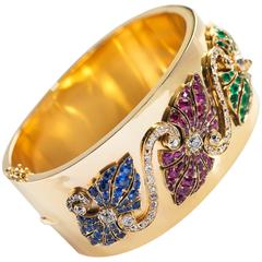 Gold Bangle with Escutcheons of Emeralds, Rubies, Sapphires and Diamonds