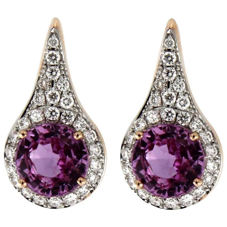 Jona design collection, hand crafted in Italy, 18 karat yellow gold stud earrings showcasing a pair of intense pink sapphires weighing 1.80 total carats, surrounded by a pear shaped frame of 52 white diamonds weighing 0.25 carats.  DIMENSIONS: 0.48