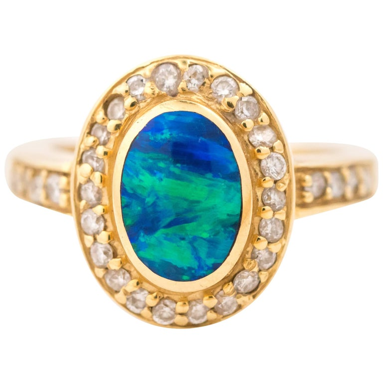 0.5 Carat Oval Opal and Diamond Halo 18 Karat Yellow Gold Ring