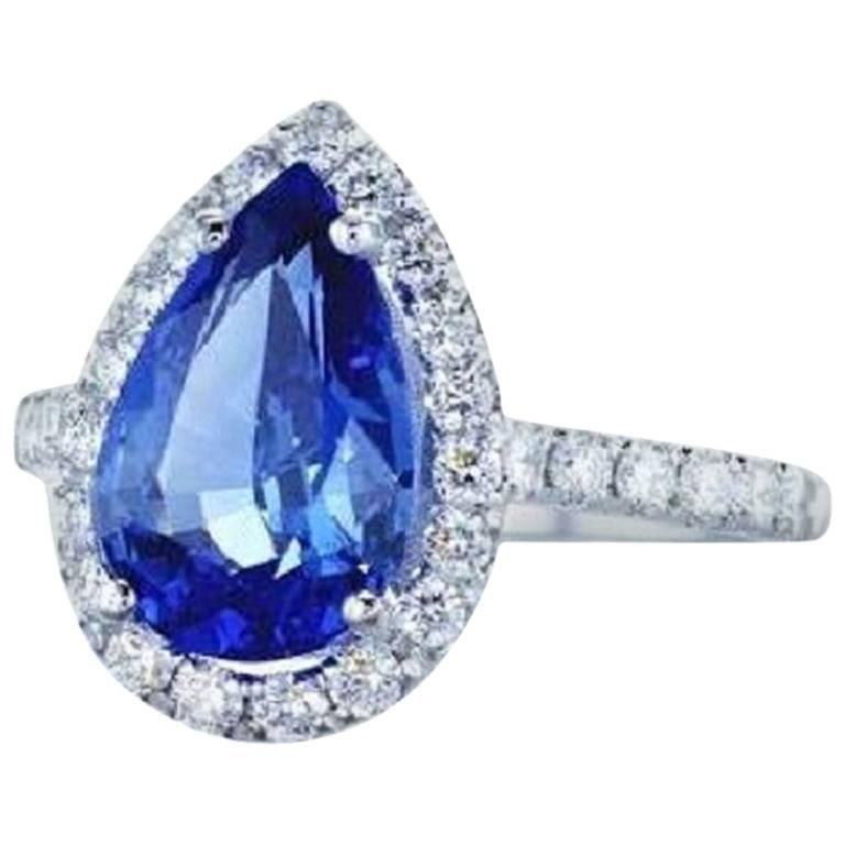 Handcrafted 3.53 Carat pear shape blue sapphire ring surrounded by  31 high quality diamonds, 0.60 Carat Total Weight and mounted on 18K white gold Ring Details:  3.53 Carat Pear Shape Blue Sapphire 31 round diamonds, 0.60 Carat total diamond