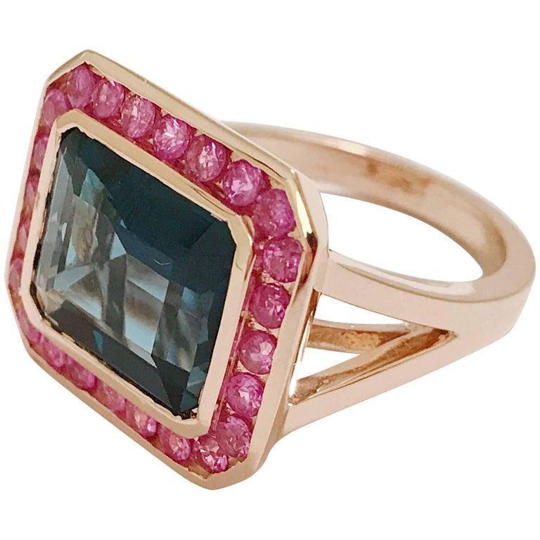 Rose Gold Bezel Set Dark Blue Topaz with Surrounding Pink Sapphire Ring