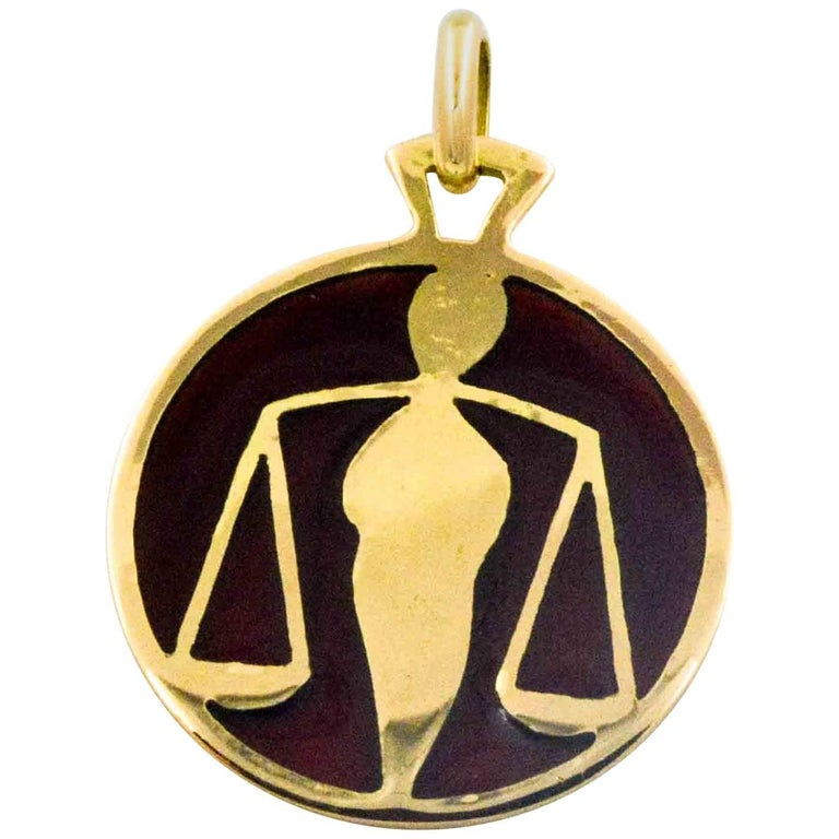 On an amber background, 18 karat yellow gold outlines the greens and yellows of the Libra zodiac sign in this Plique a Jour pendant. A master craftsman in the art of Plique a Jour created this hand enameled glass Libra pendant. Light weight