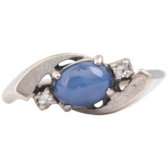1950s 0.25 Carat Blue Star Cabochon Sapphire and Diamond Bypass Ring