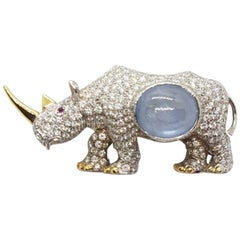 Rhinoceros Broach in White and Yellow Gold with Diamonds and a Sapphire Cabochon